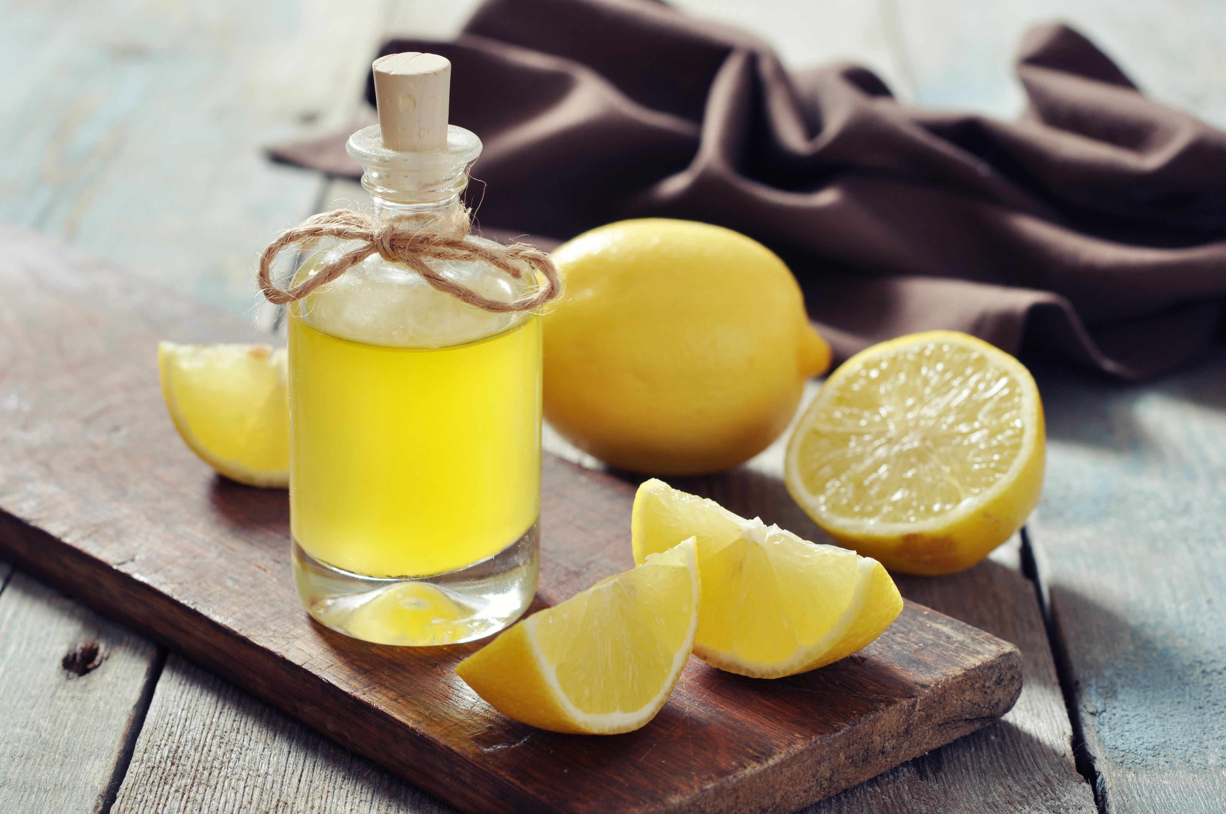 Lemon oil in a glass bottle with fresh lemon on wooden background